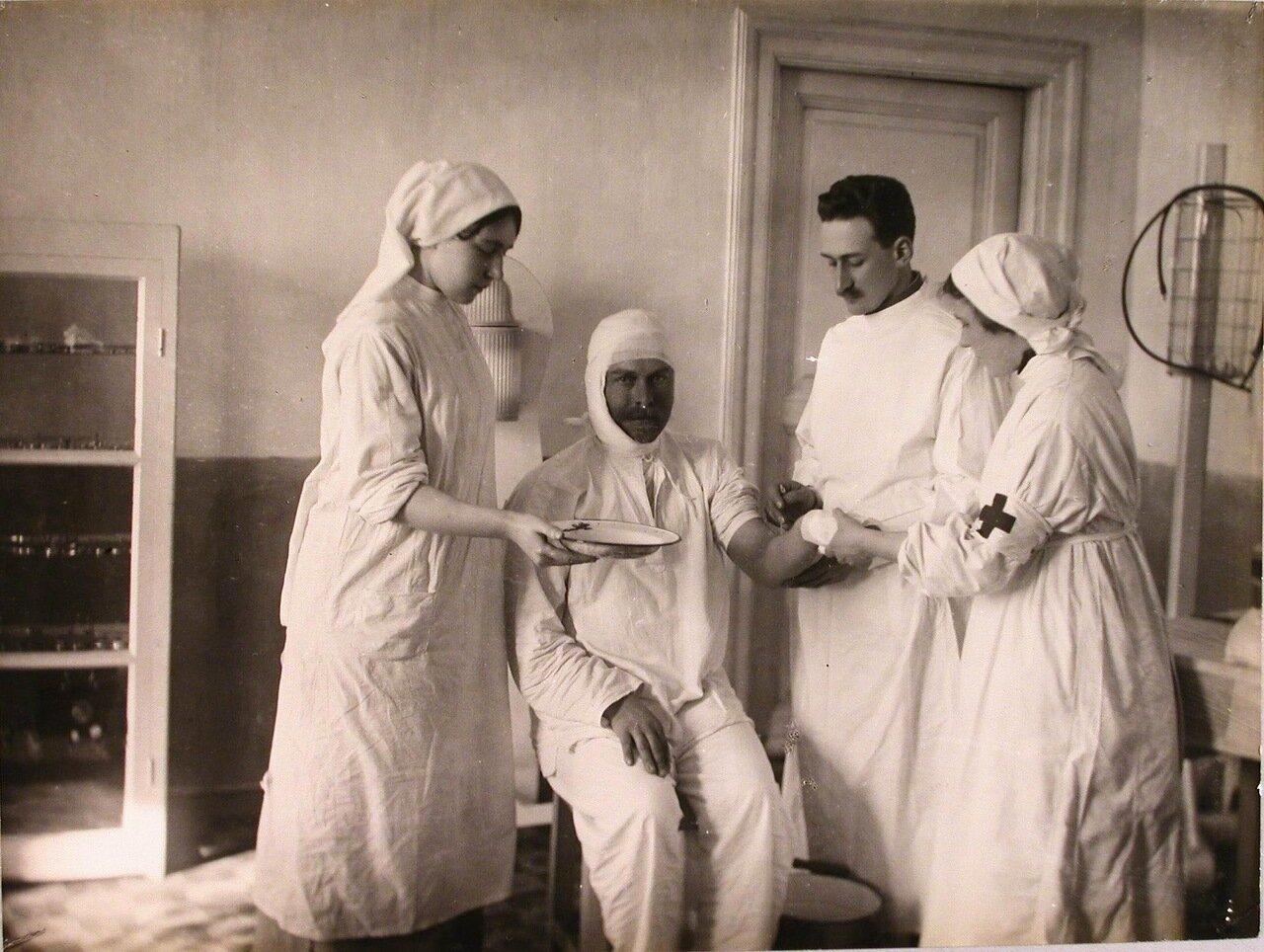 12. Врач и медицинские сёстры в процедурном кабинете делают укол раненому