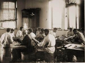 Группа призреваемых за работой в сапожной мастерской.