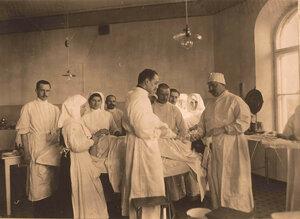 Группа врачей и сестёр милосердия во время проведения операции раненому в ногу;крайний справа- профессор И.Х.Дзирне.