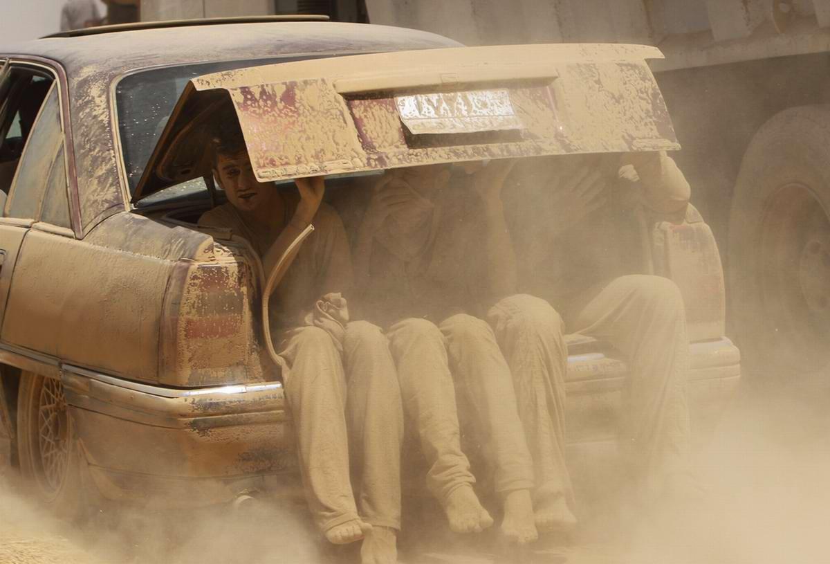 Пыльные беженцы, едущие в багажнике легкового автомобиля