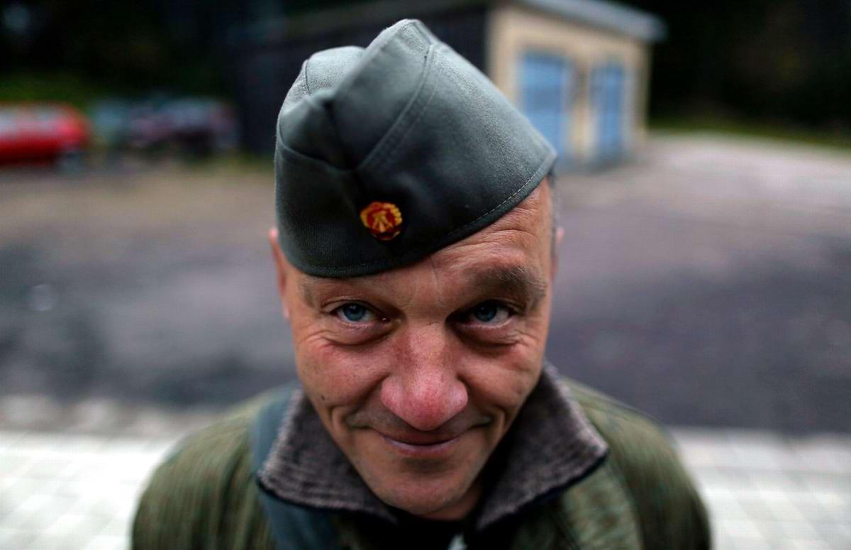 Мужчина в форме солдата Национальной народной армии позирует фотографу во время экскурсии
