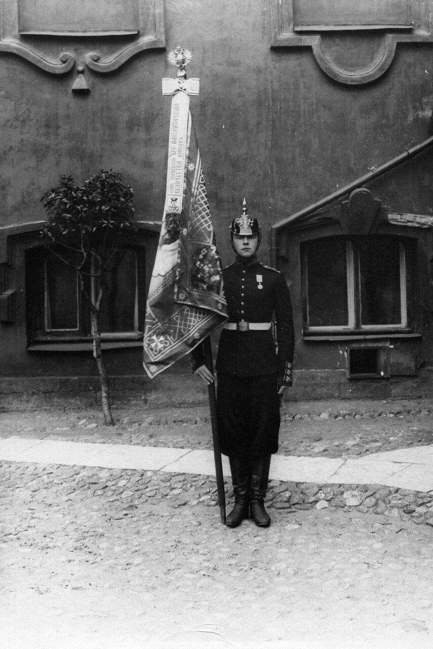 19. Паж со знаменем перед зданием корпуса