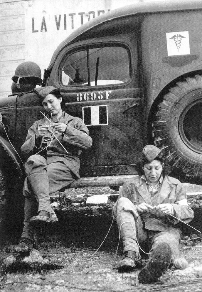 Two women of the Free French ambulance corps take time out for knitting while awaiting their next call somewhere on the Italian front in 1944.jpg