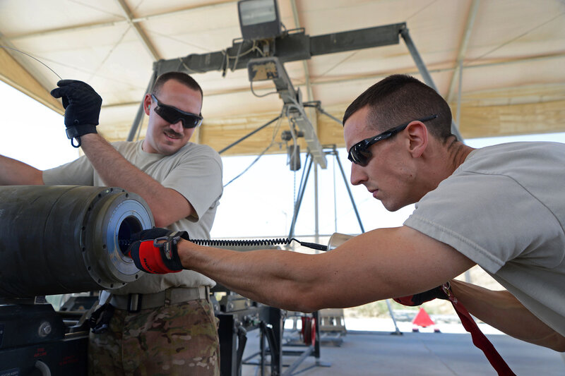U.S. Air Force Senior Airman Christopher Reed, a munitions systems technician currently assigned to the 455th Expeditionary Maintenance Squadron, works with Senior Airman Brandon Graves, a munitions systems technician string connection wire through a bomb