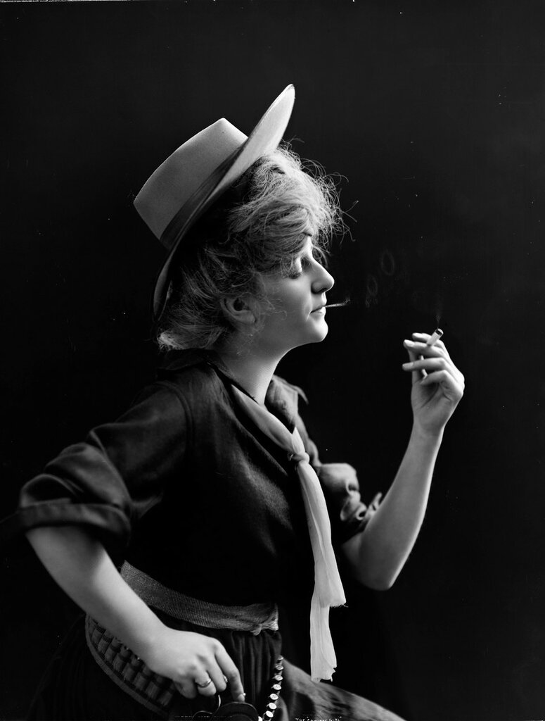 Studio portrait of a woman dressed as a cowgirl. She looks at and contemplates a cigar that she holds in her hand. 1903.