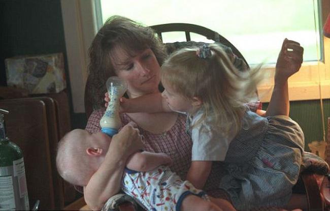 Старшая дочь, Микаэла, которая родилась загод доблизнецов, помогает маме кормить малышей.