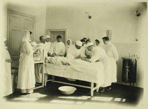 Врачи и медицинские сестры за перевязкой раненого в перевязочной тылового госпиталя (открытого в здании Духовной семинарии)