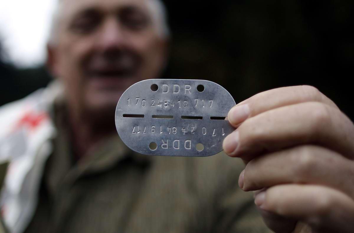 Личный жетон солдата Национальной народной армии ГДР в руках одного из работников бункера-музея