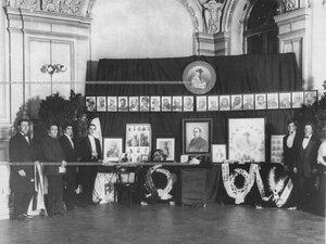 Группа артистов Александринского театра в фойе у стенда с портретами Далматова Василия Пантелеймоновича в день чествования памяти артиста.