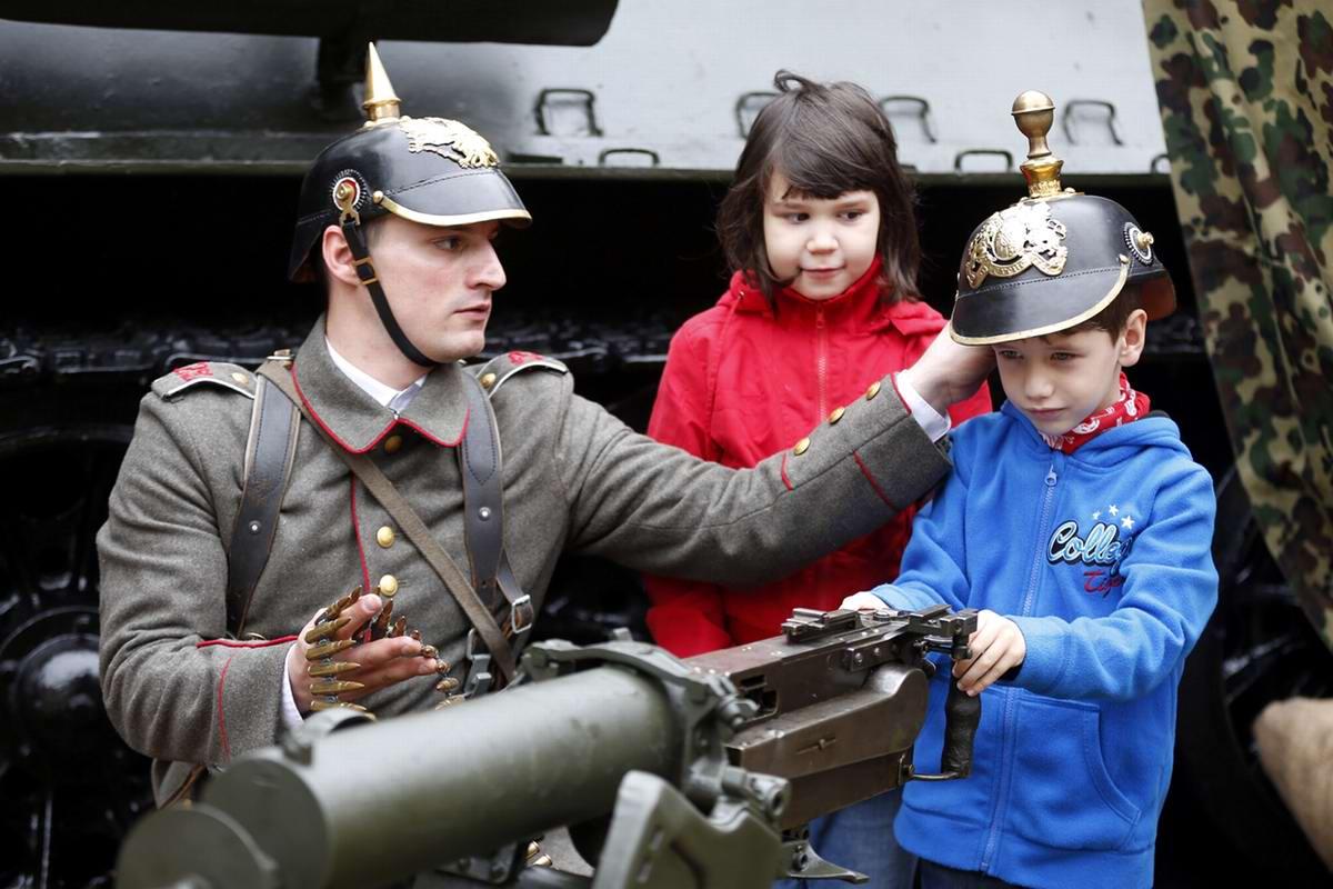Участник реконструкции в военной униформе времен Первой мировой войны вместе с детьми в Национальном военном музее Румынии в Бухаресте