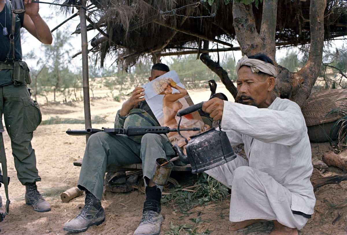 Вьетнамец заваривает чай в то время, пока американский морской пехотинец занимается лицезрением похотливой красотки с эротического плаката