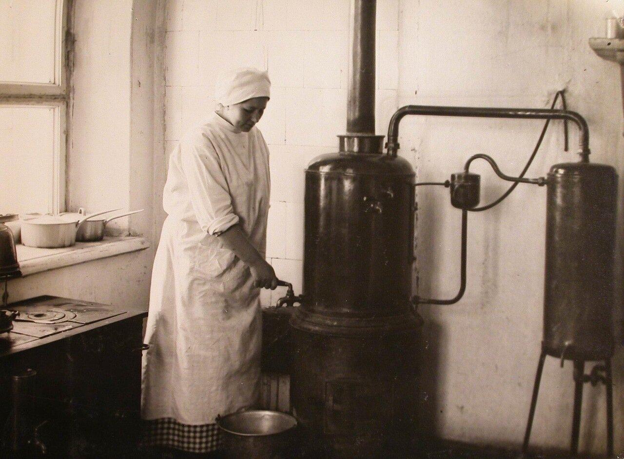 33. Медицинская сестра наливает кипячёную воду из титана в ведро
