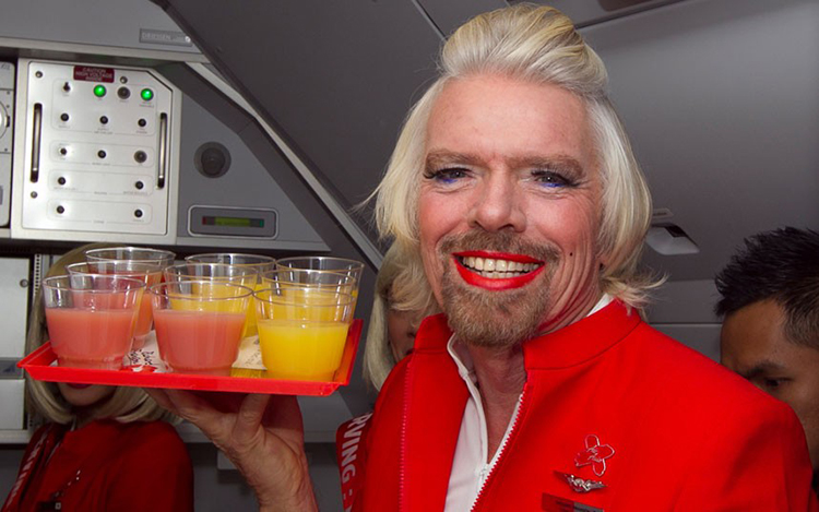British billionaire Richard Branson poses with a tray of drinks onboard an AirAsia flight bound for Kualu Lumpur while working as a flight attendant at Perth Airport on May 12, 2013. Branson honoured a losing bet with AirAsia group chief Tony Fernandes ov