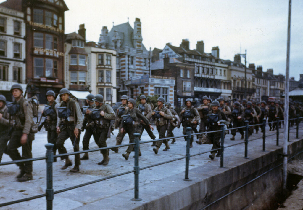 These American troops are marching through the streets of a British port town on their way to the docks where they will be loaded into landing craft for the big assault.