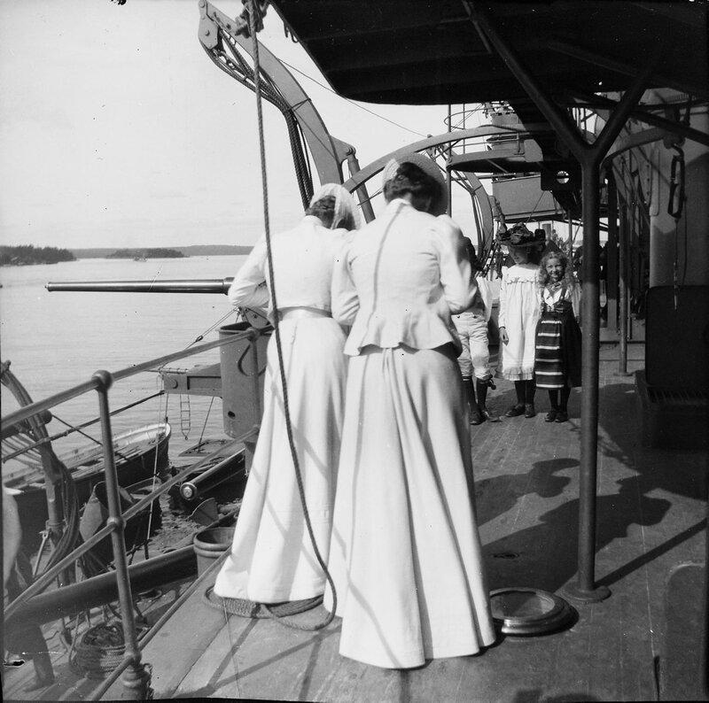 Девочки на корабле позируют для двух фотографов. Дети носят шведские народные костюмы, 1900