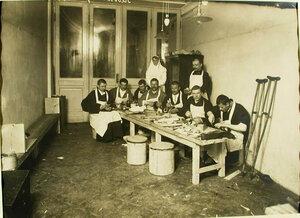 Группа выздоравливающих и сестра милосердия в сапожной мастерской лазарета