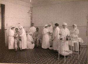 Медицинские сестры за перевязкой раненых в перевязочной лазарета,устроенного АрмянскимБлаготворительнымобществом.