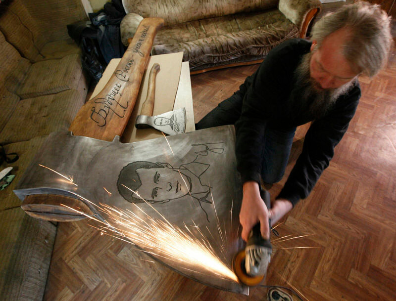 Russian artist Vasily Slonov sharpens an axe decorated with a portrait of Russian businessman and politician Mikhail Prokhorov in his workshop as he prepares for an exhibition of his new art project in Russia's Siberian city of Krasnoyarsk December 15, 20