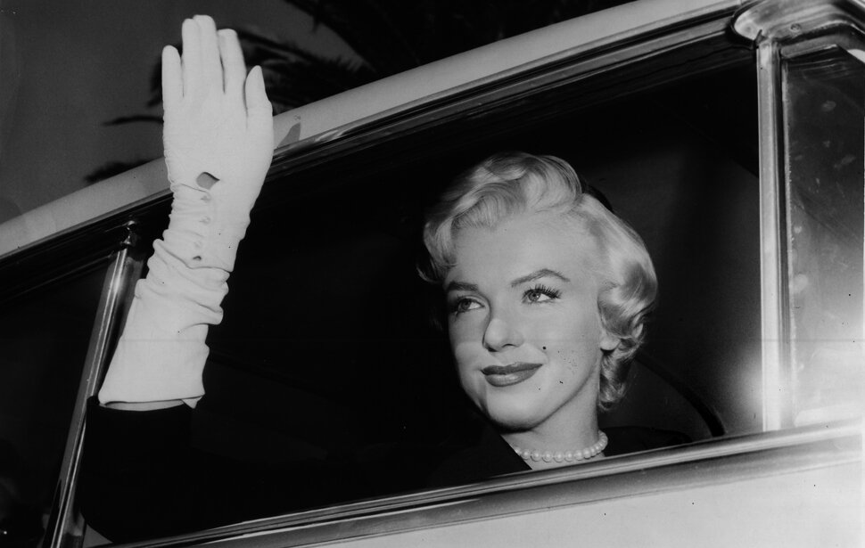 Marilyn Monroe waves from a car after a court hearing for her divorce from Joe DiMaggio, October 27, 1954.
