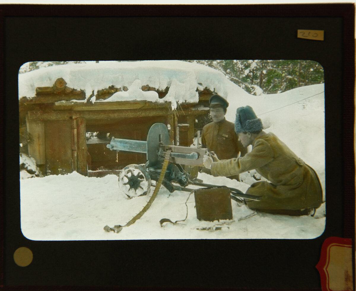 Русский пулеметчик рядом с другим военным перед заснеженным бункером