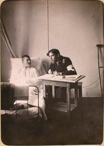 Студент Политехнического института пишет письмо под диктовку раненого солдата в одной из палат госпиталя, оборудованного в здании института.