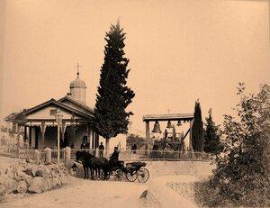 Местные жители у входа в церковь Свмч. Феодора Тирона в Верхней Аутке, близ Ялты; справа - звонница.