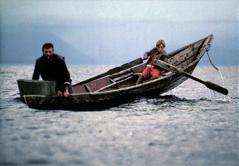 Рыбак Вячеслав Басов ставит сети, в то время как его сын, 10-летний Толя, управляет лодкой при помощи самодельных весел
