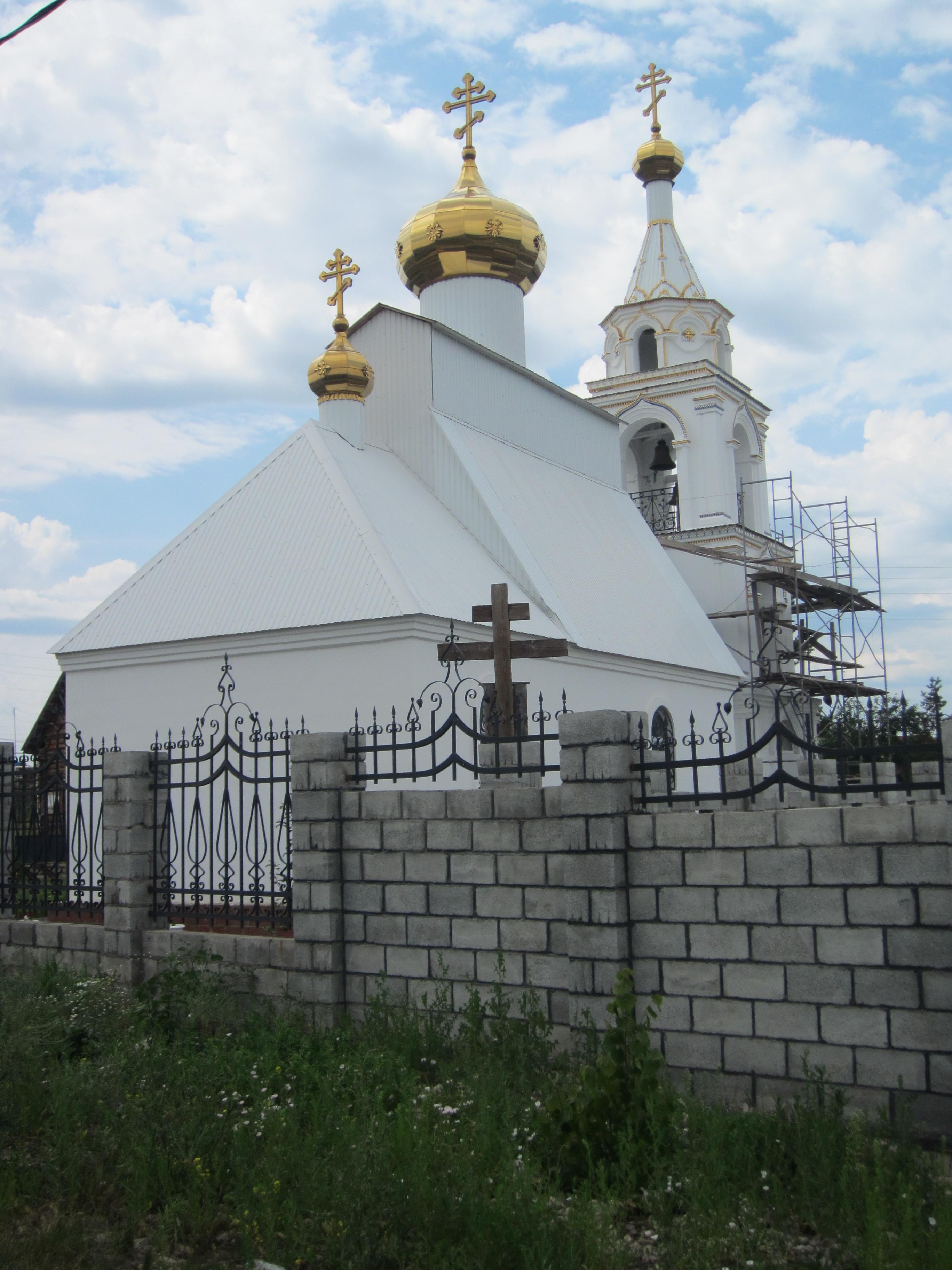 За оградой виднеется поклонный крест (09.07.2014)