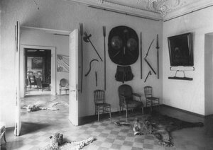 Часть кабинета со старинным оружием на стене.