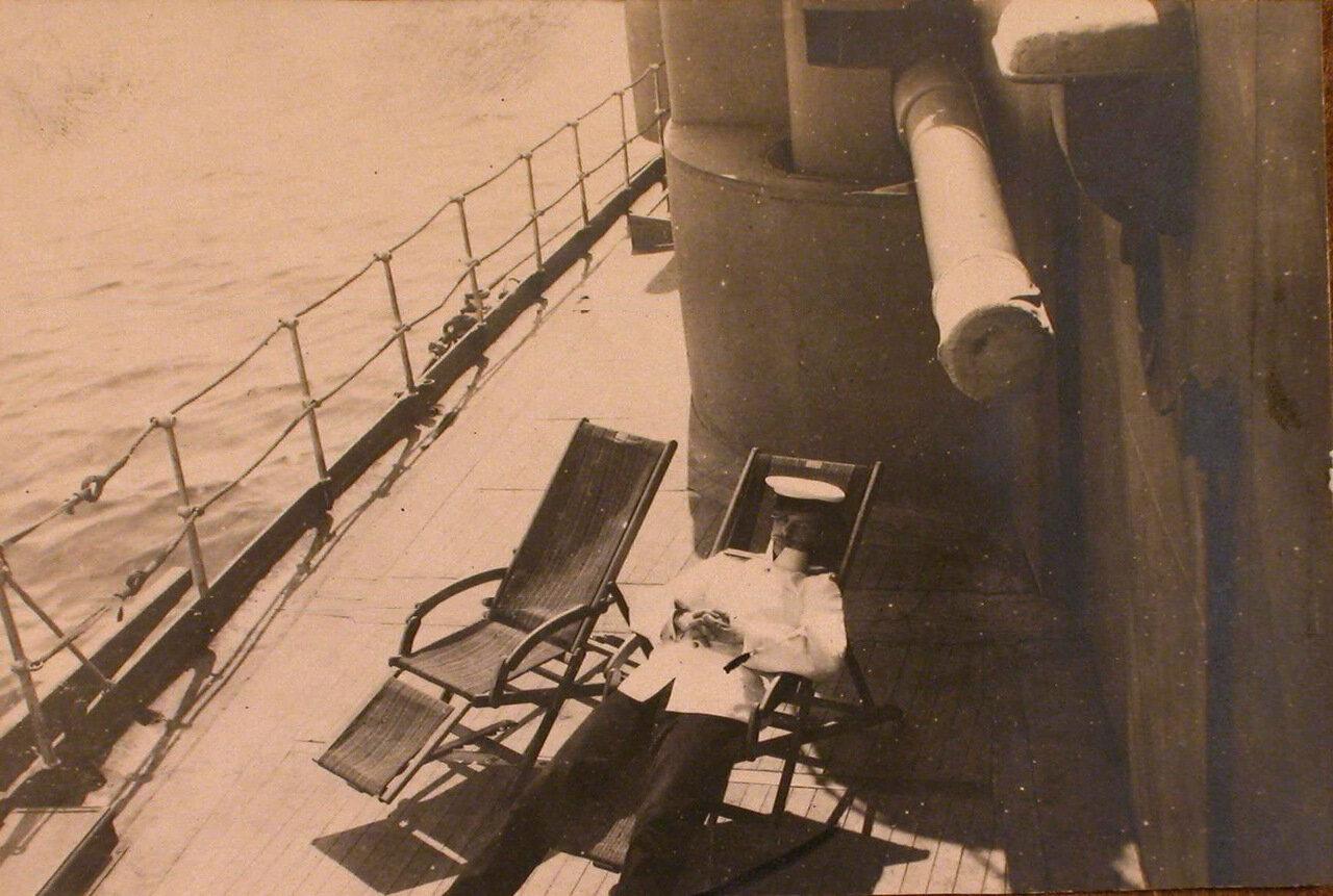 18. Офицер в шезлонге на палубе линейного корабля  у казематного орудия