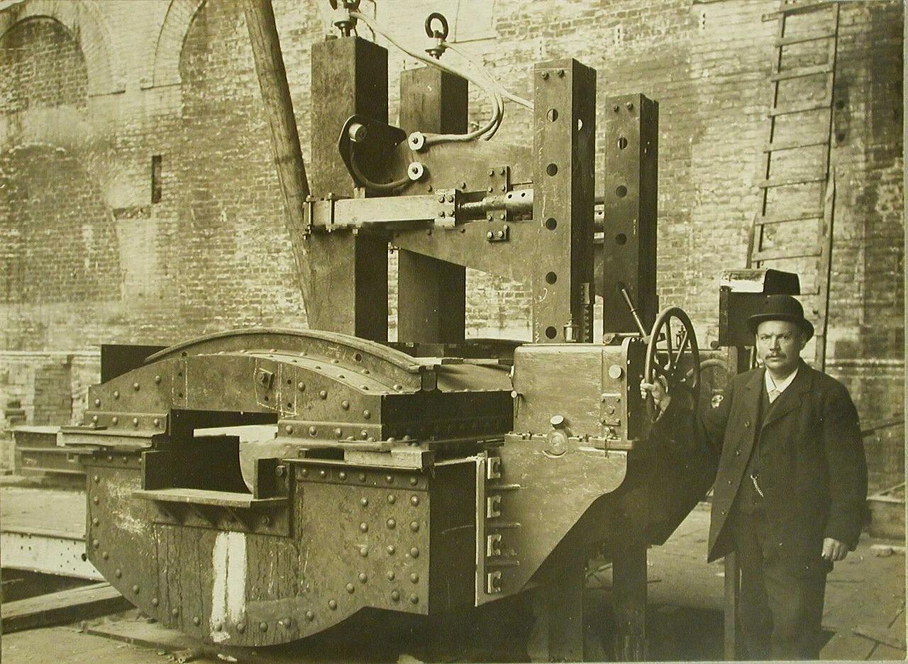 14. Заводской служащий у станины печи, установленной в одном из цехов. 20 октября 1909