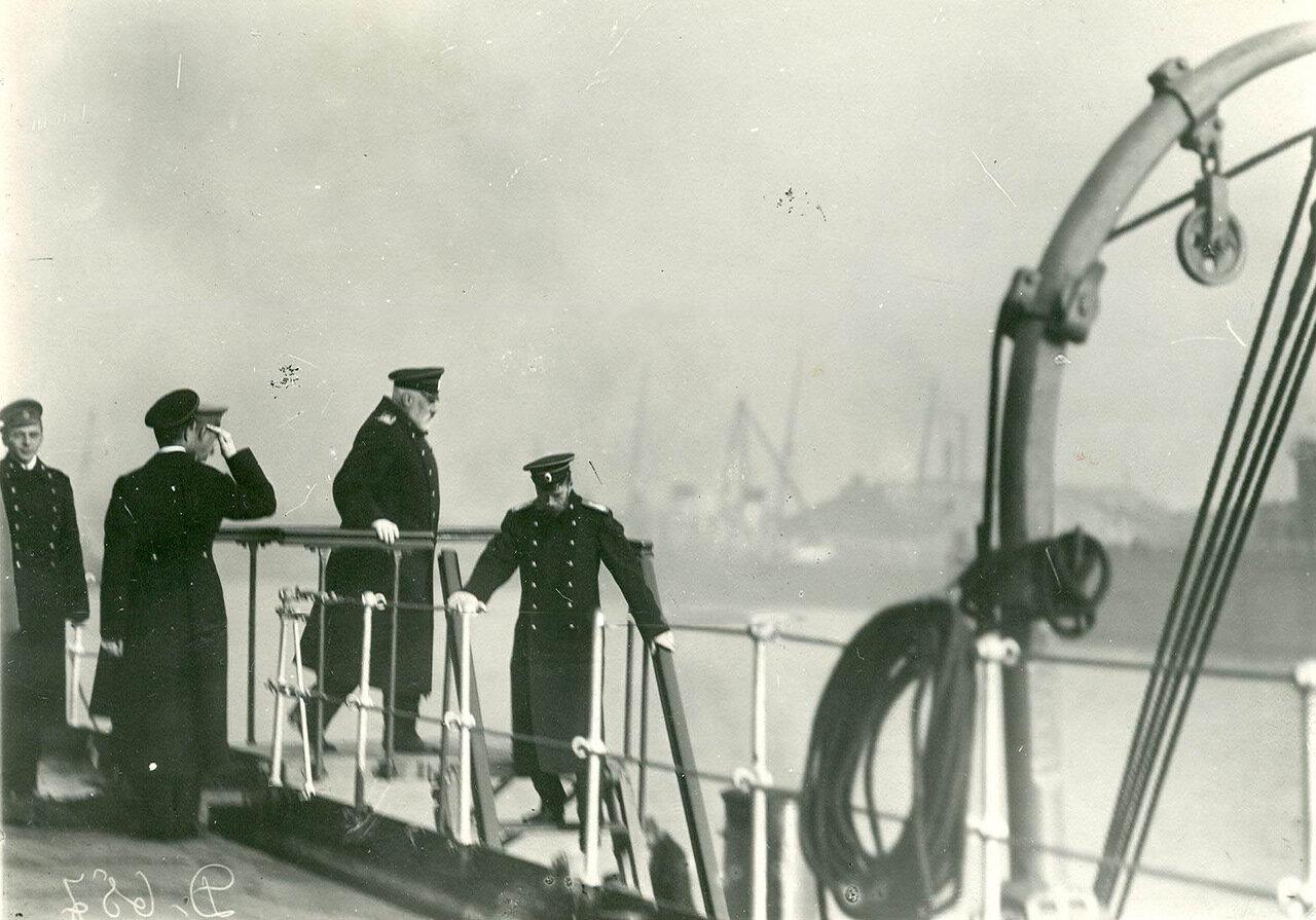 23. Император Николай II и сопровождающие его лица спускаются по трапу с борта линкора «Петропавловск» на катер «Петергоф»