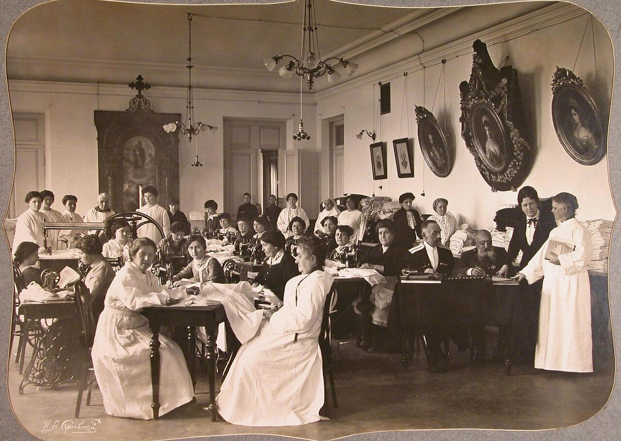 17. Женщины-волонтеры и представители Красного Креста за шитьем белья в зале общины