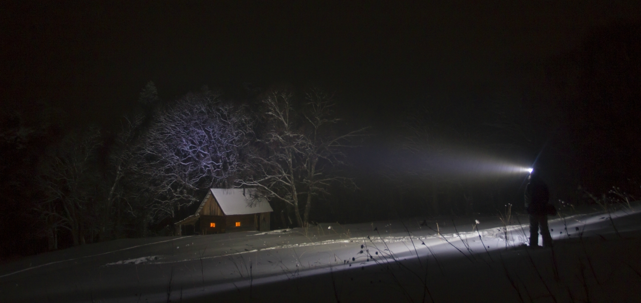 hut and hiker at night in winter mountain