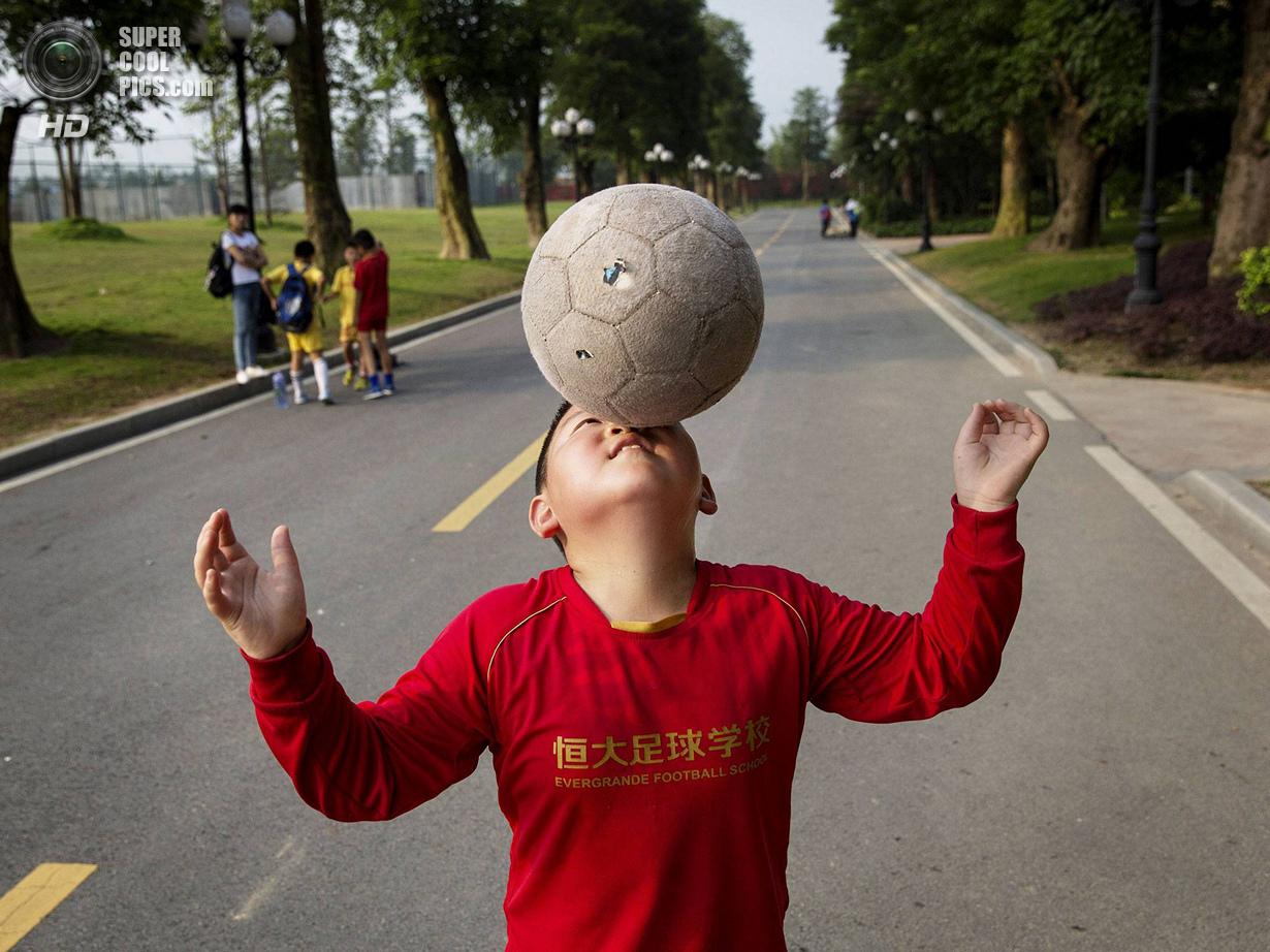 Китай. Цинъюань, Гуандун. 13 июня. Юный китайский футболист демонстрирует свои умения. (Kevin Frayer
