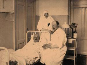 Врач и сестра милосердия у постели раненого офицера в 10-й палате.