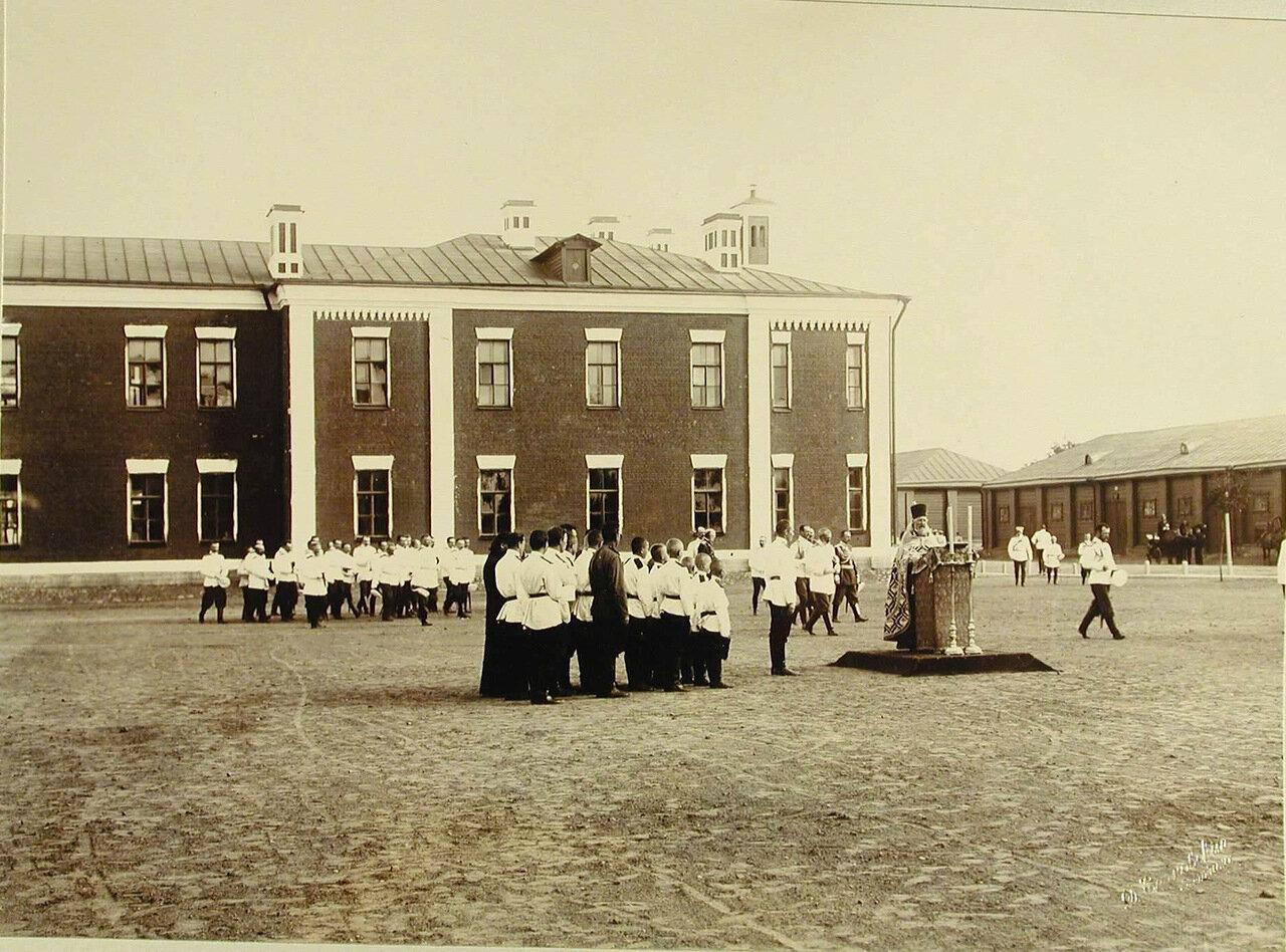 04. Священник и группа певчих на плацу во время смотра артиллерийских частей; справа (идет) - император Николай II