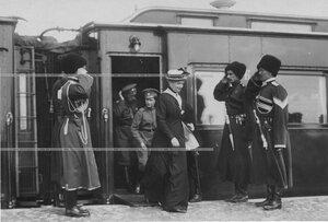 Императрица Александра Федоровна, цесаревич Алексей Николаевич и император Николай II выходят из вагона поезда по прибытии в ставку. Офицеры собственного его императорского величества конвоя приветствуют императорску