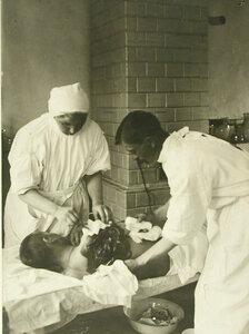 Врач и сестра милосердия перевязывают рану от разрывной пули раненому в  операционной  Екатеринбургского этапного лазарета