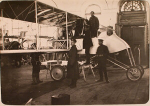 Солдаты и механики авиароты у монтируемого корпуса летательного аппарата в сборочной мастерской.