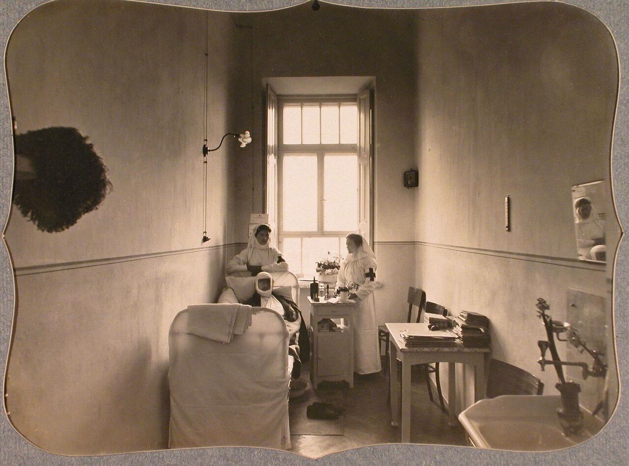 40. Сестры милосердия и раненый офицер в двухместной палате лазарета общины