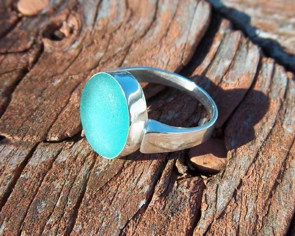 серебряный перстень с бирюзоввой вставкой из стекла обкатанного морем на фоне старой древесины
