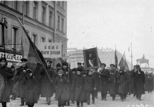 Манифестанты с правительственными флагами, плакатами и портретом императора Николая II проходят мимо Николаевского вокзала по Невскому проспекту.