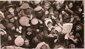 Беженцы у перевязочно-питательного поезда №13, организованного отрядом Красного Креста В.М.Пуришкевича получают хлеб (снимок сделан с крыши вагона).