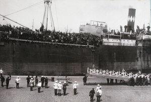 Портовые рабочие готовят трап для спуска прибывших пассажиров- эвакуируемых с Дальнего Востока нижних чинов и запасных.