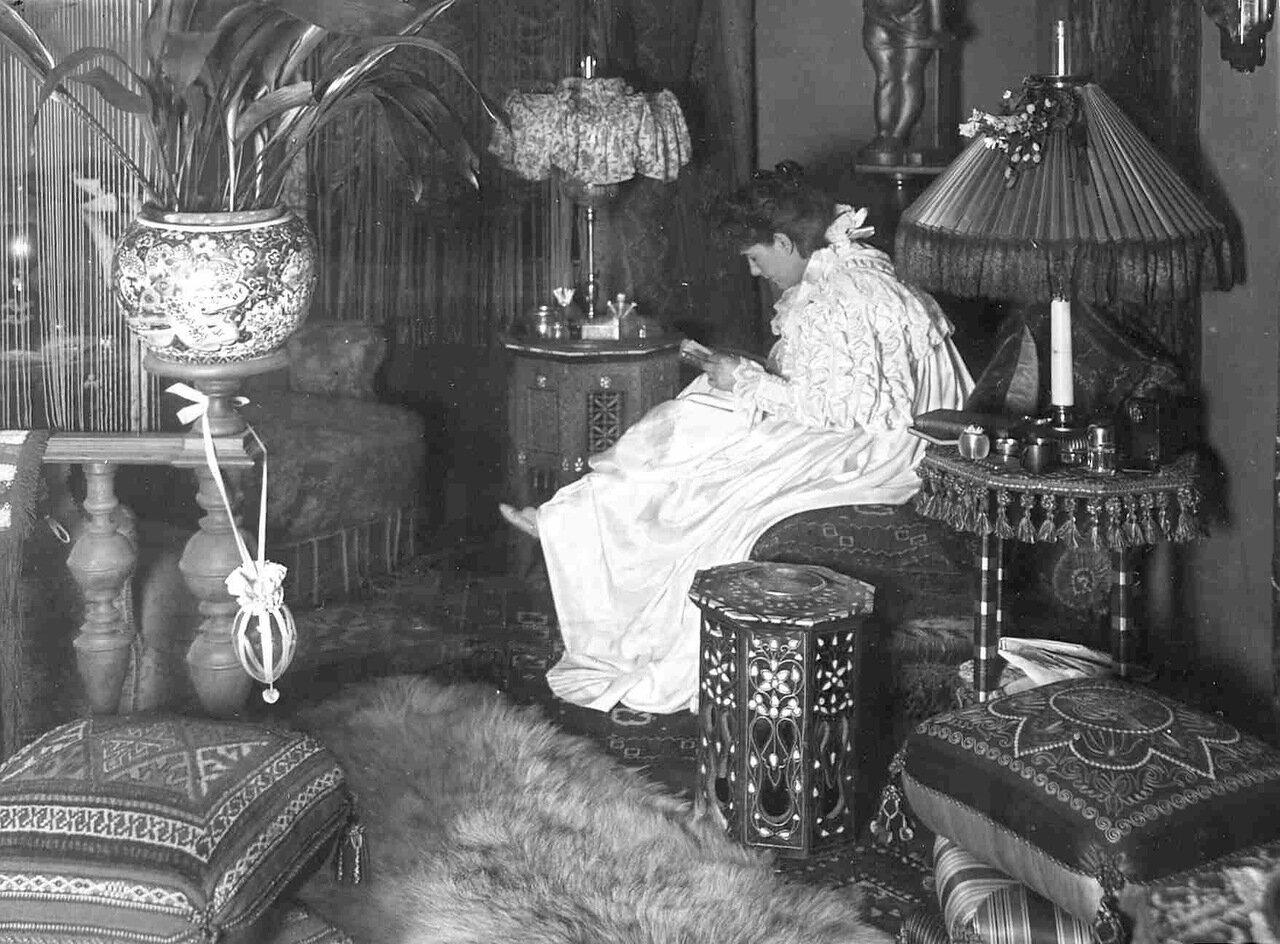 15. Гостиная; на первом плане - женщина за чтением