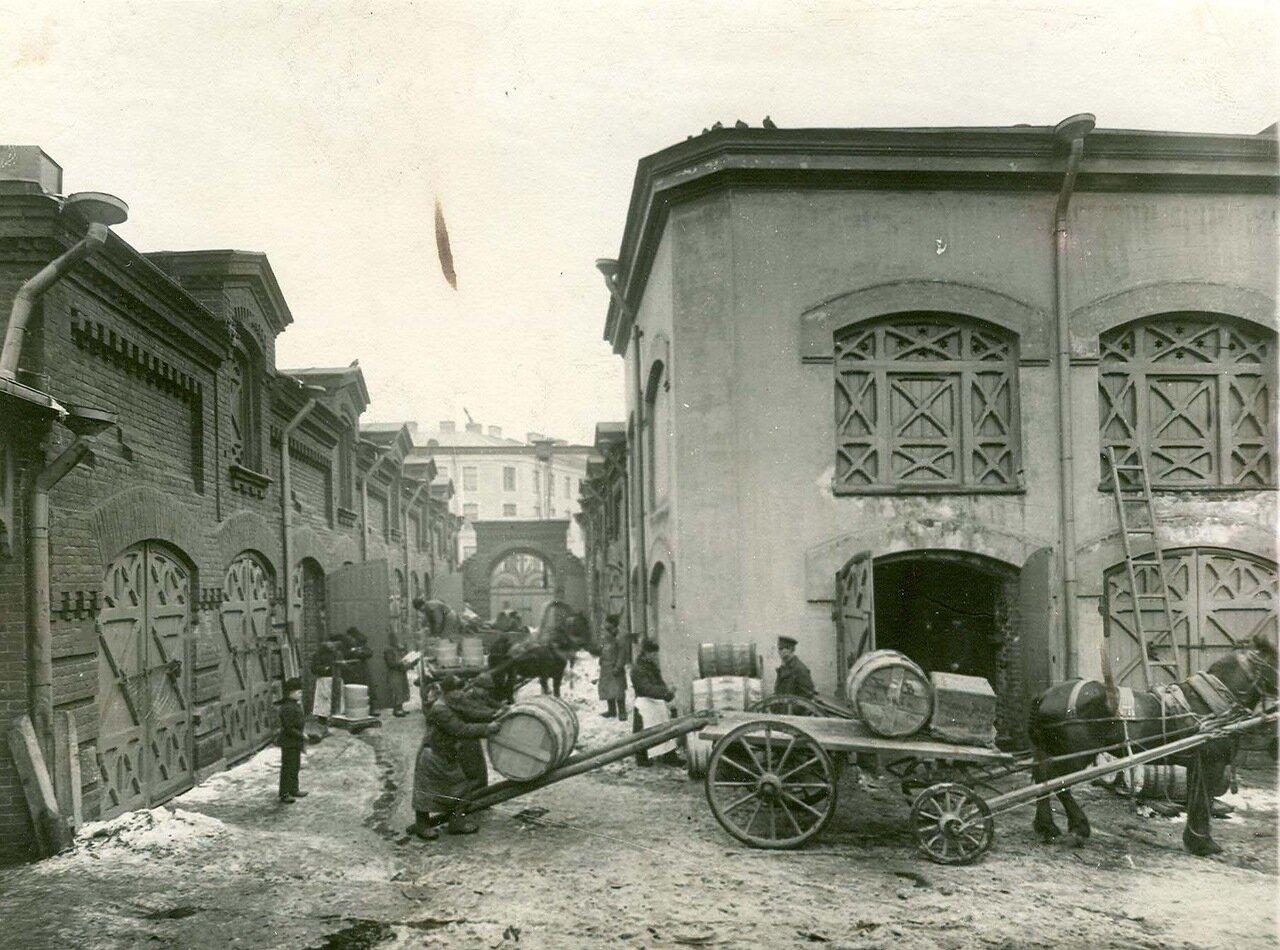 06. Рабочие во дворе завода грузят на телеги бочки для отправки в Москву