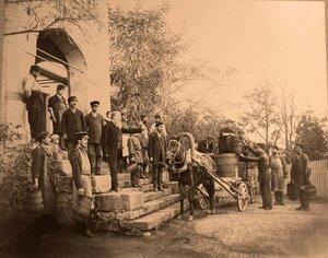 Группа местных жителей - работников фермы за разгрузкой урожая винограда.