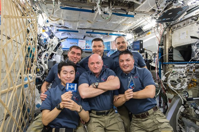 The Expedition 45 crew gathers inside the Destiny laboratory to celebrate the 15th anniversary of co