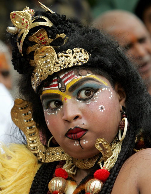 An activist dressed up as Shiva takes part in a protest in New Delhi July 5, 2006. (Photo by Kamal K